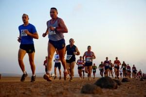 Sportivi alergând pe suprafață naturală